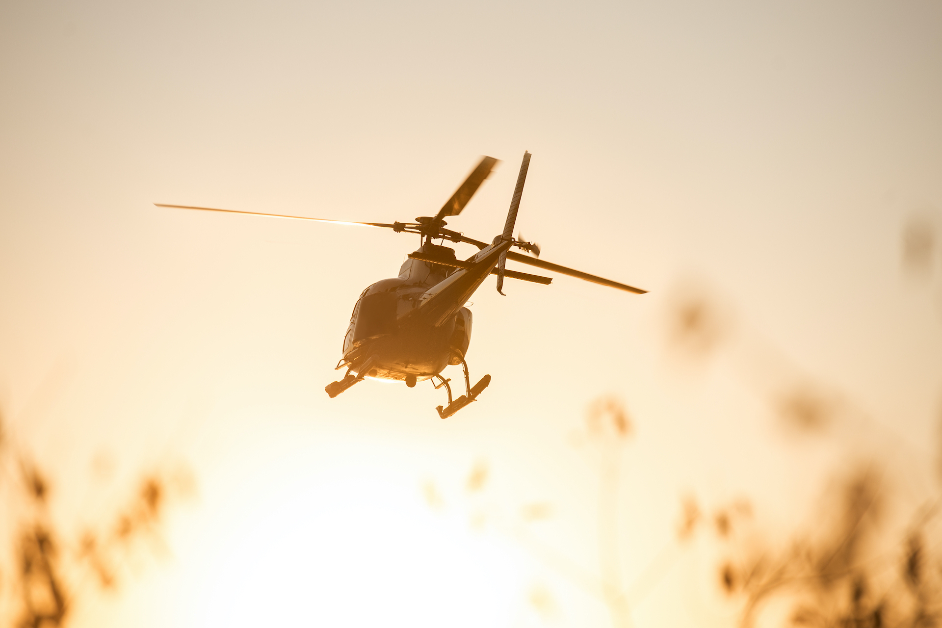 picture of helicopter flying into the sunset