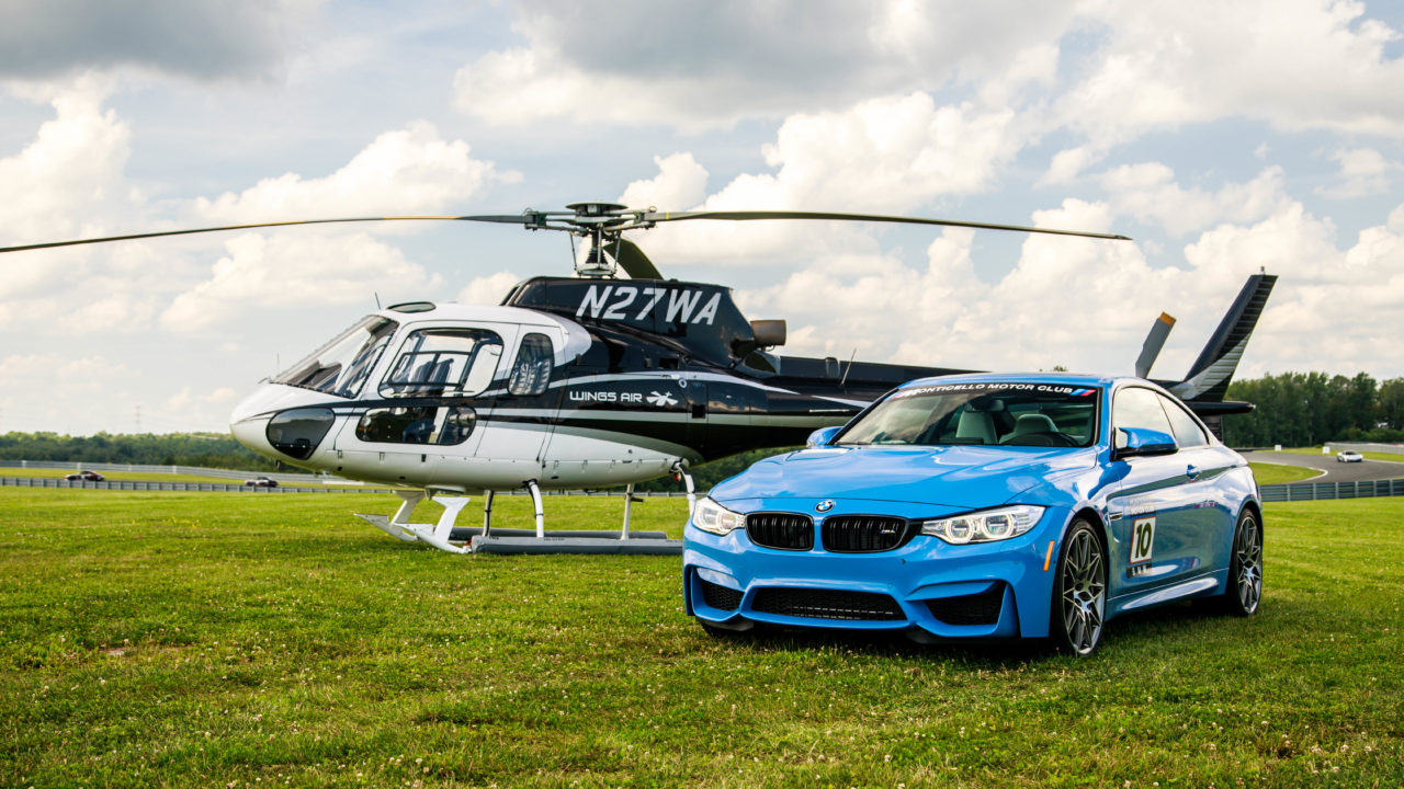 picture of a blue car next to a helicopter on a grass field