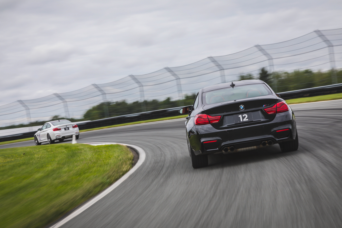 black bmw racing behind a white bmw on a race track