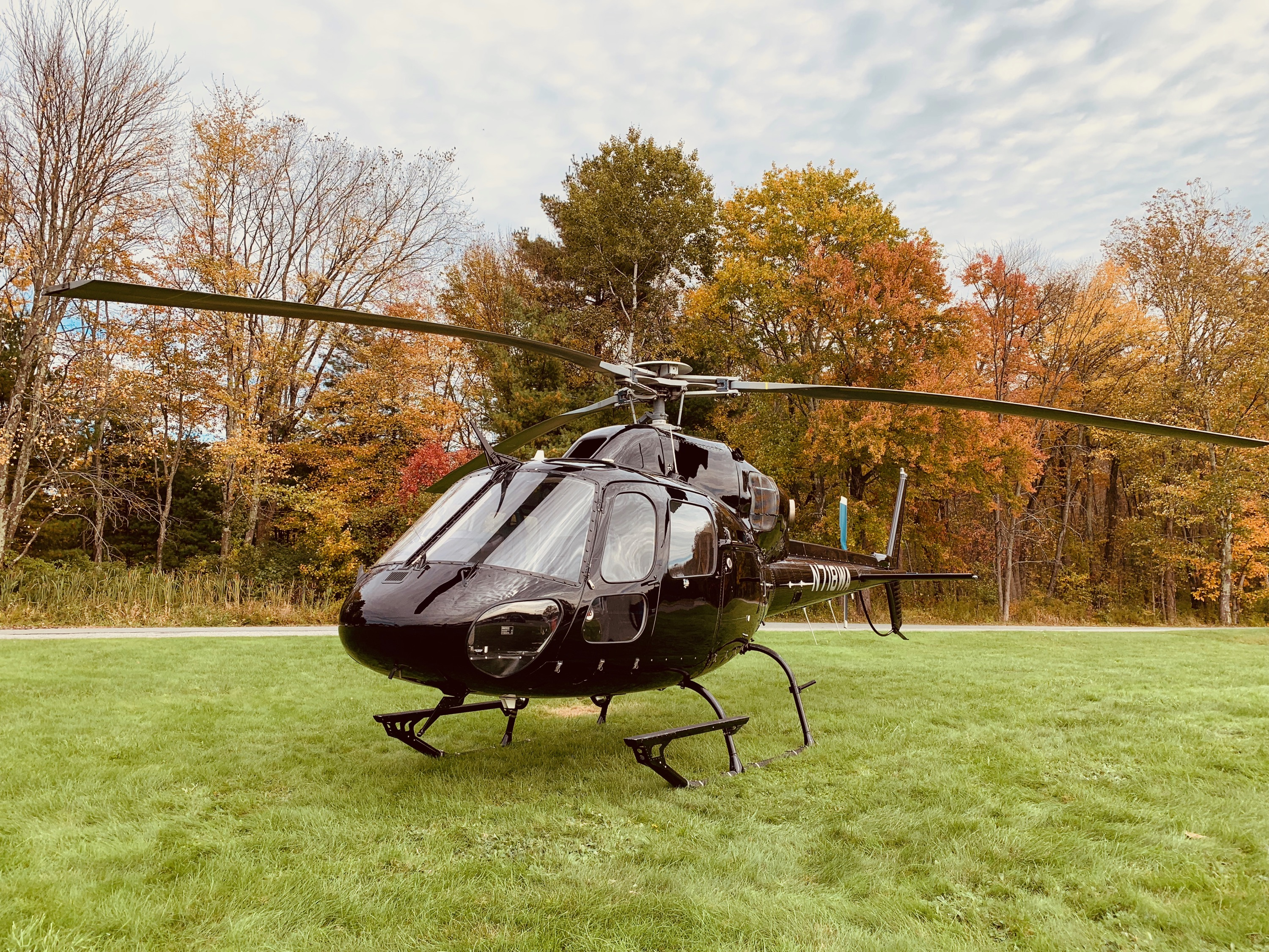 black helicopter on a grass field about to take off with trees in the background during fall