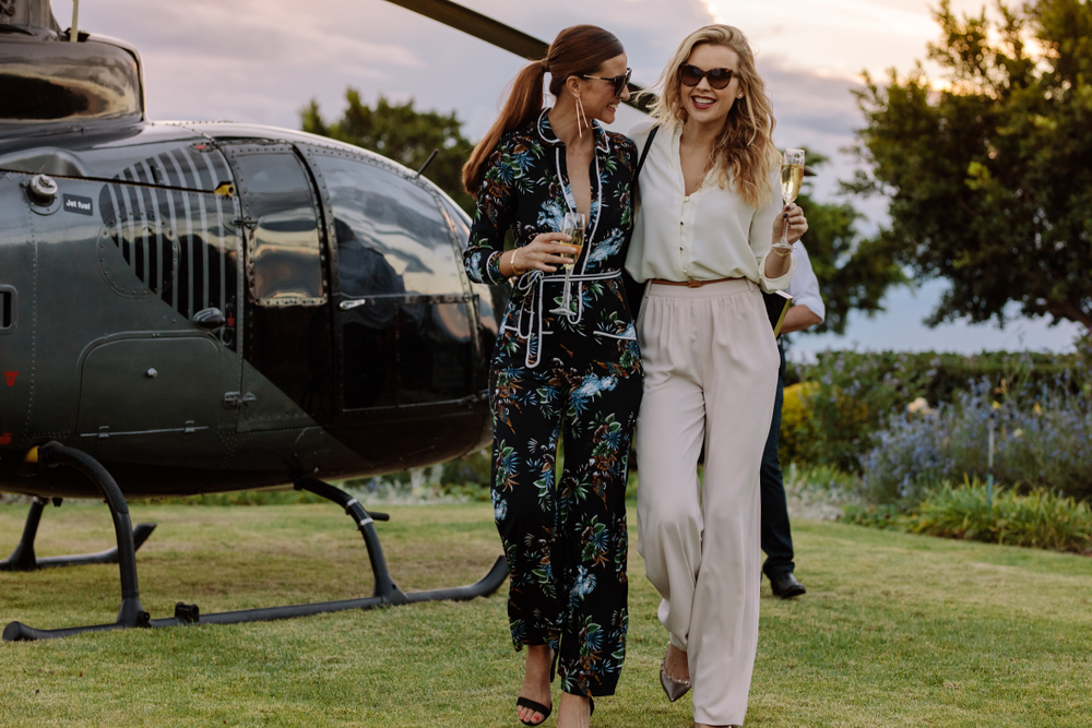 2 women walking close by each other leaving from a helicopter sitting on a grass field during the evening