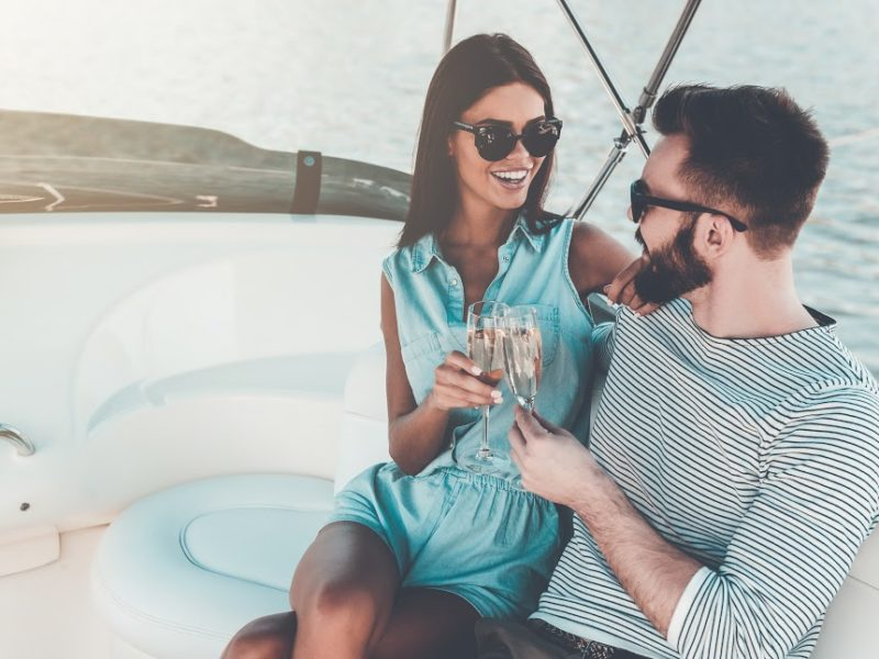 couple sitting together on a yacht holding wine glasses