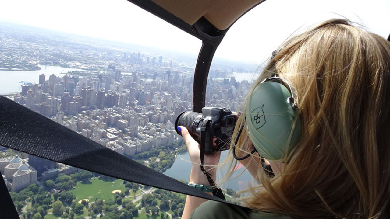 girl taking pictures with her camera of an aerial view of nyc from a helicopter cockpit