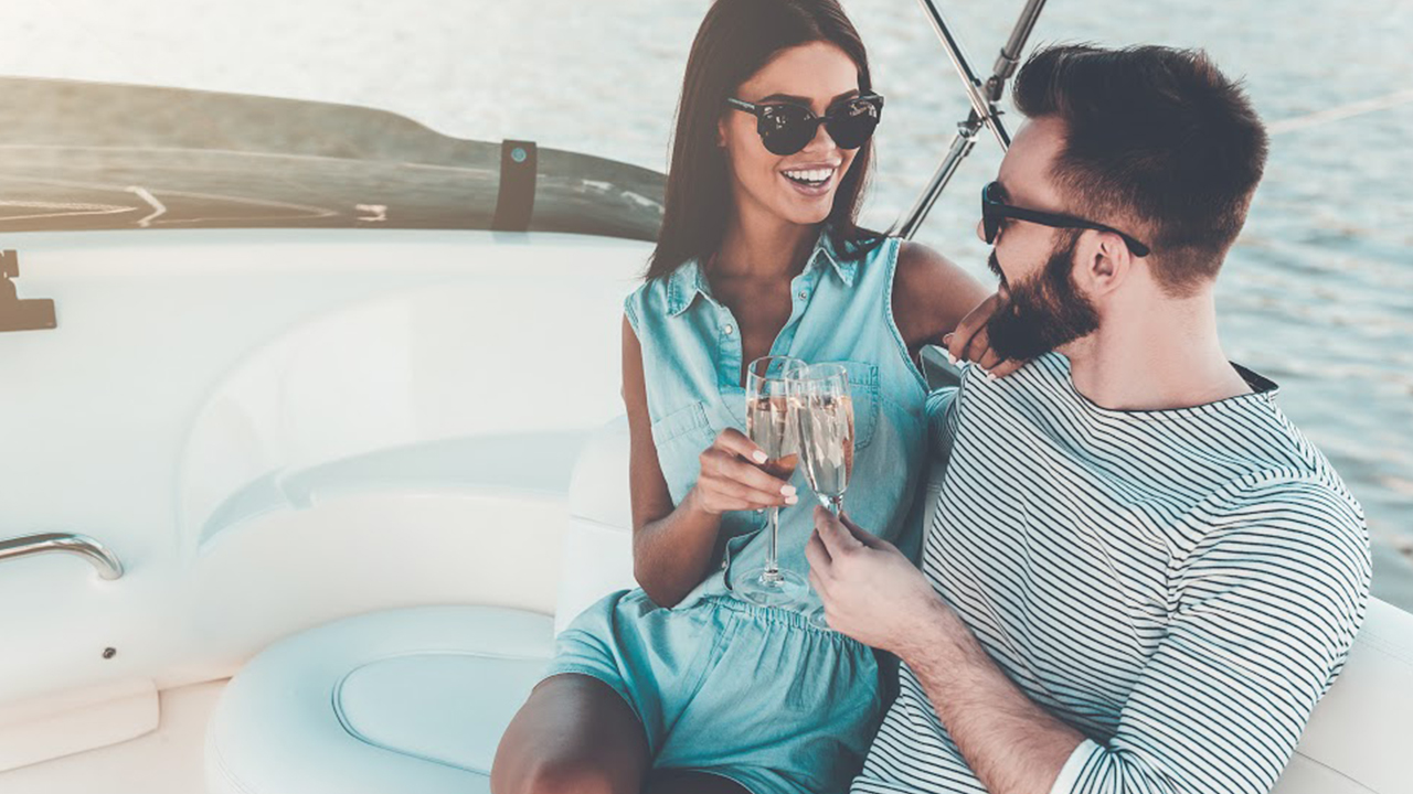 man and woman sitting together smiling on a yacht and holding champagne glasses