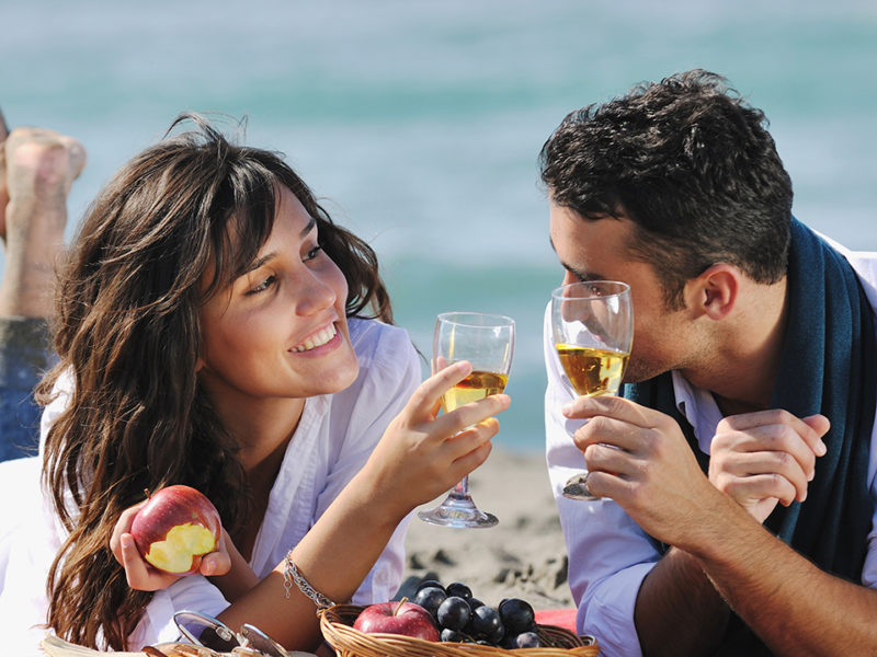 couple on a romantic picnic drinking champagne