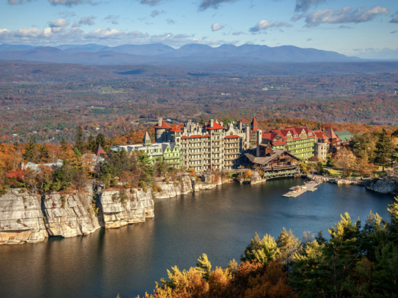 hotel on a hill overlooking a lake during fall